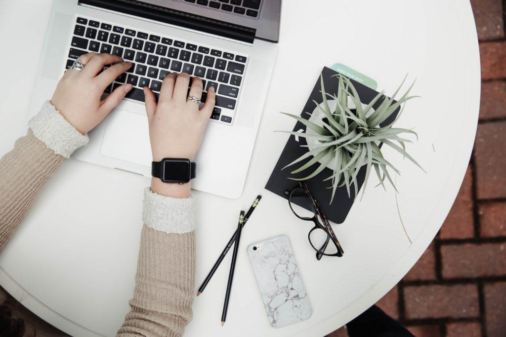 女性がノートパソコンでタイピングをしている画像