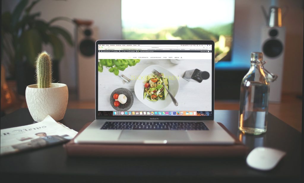 机の上にノートパソコンがありWEBサイトが開かれている写真