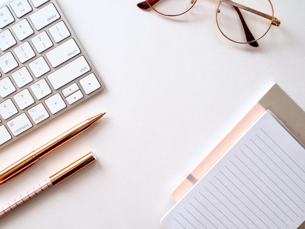 机の上にお洒落なパソコンと文房具と眼鏡が並んでいる写真