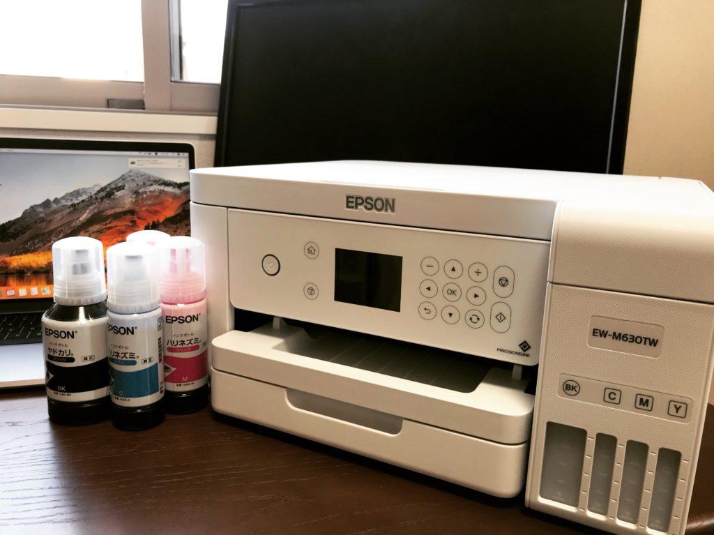 白いプリンターとインクが机の上に置いてある風景