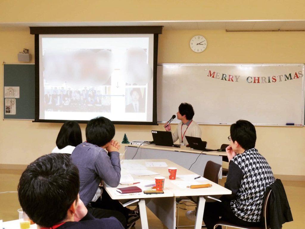 男性がスクリーンを見ながら講義をし数名が話しを聞いている画像