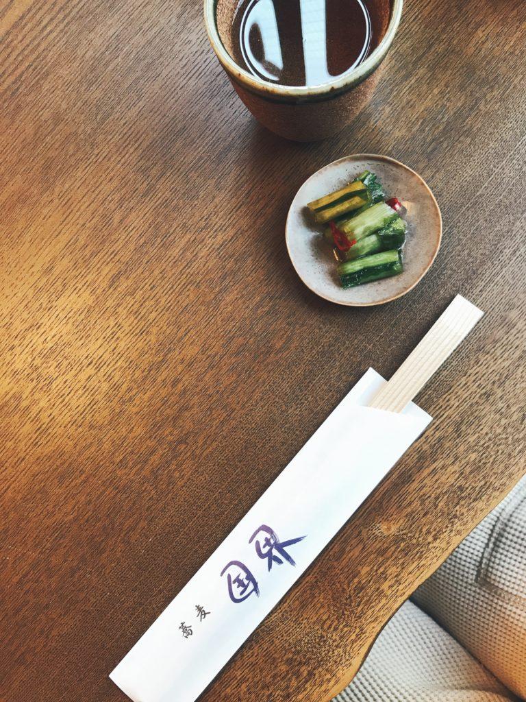 ラーメン国界の机の上にお箸と漬物とお茶が置いてある写真