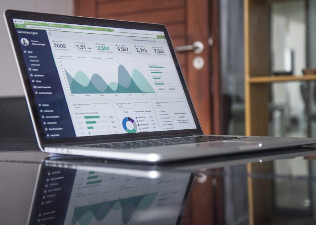 机の上にノートパソコンがありグラフが表示されている画像