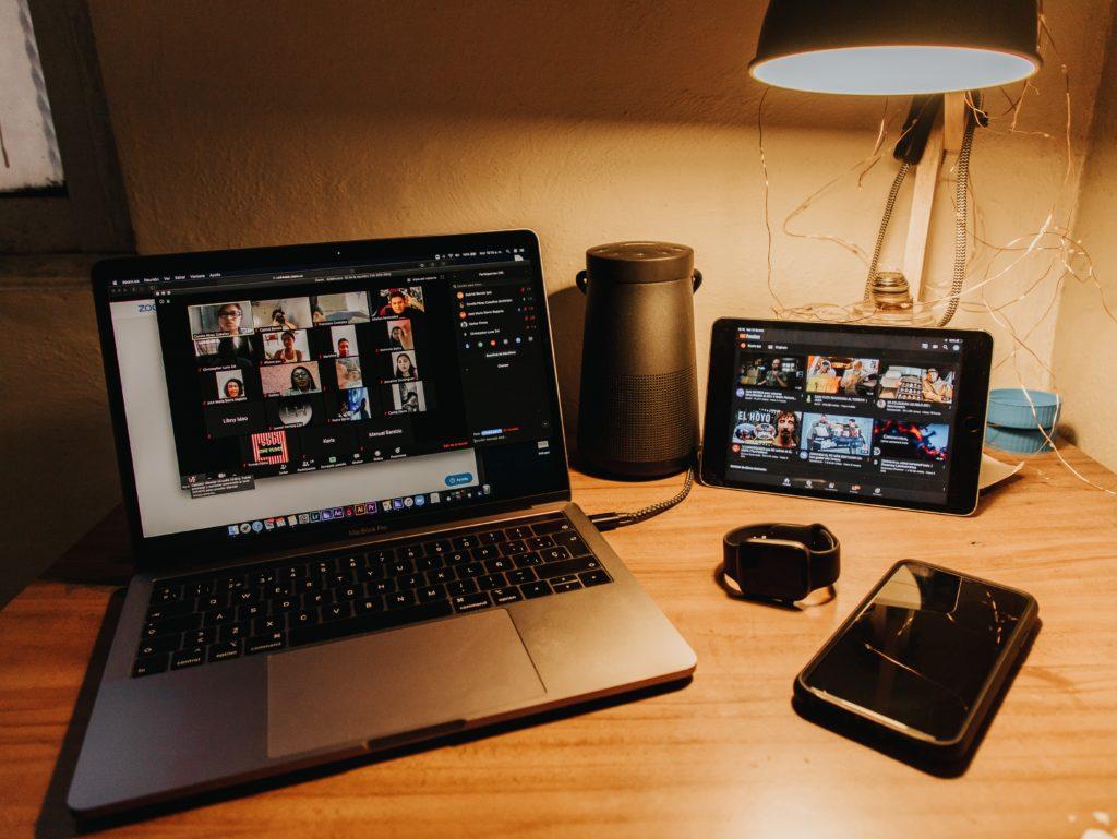 机の上にノートパソコンがありTV会議が行われている写真