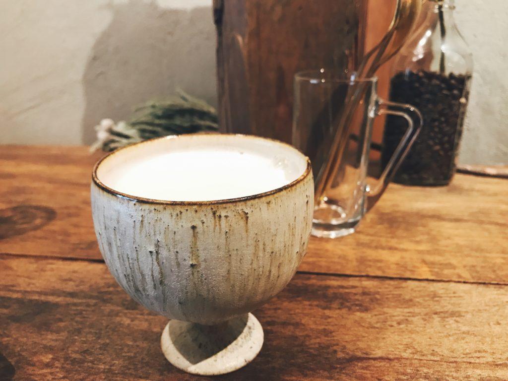 お洒落なカフェの机の上にある丸いコップに入った牛乳