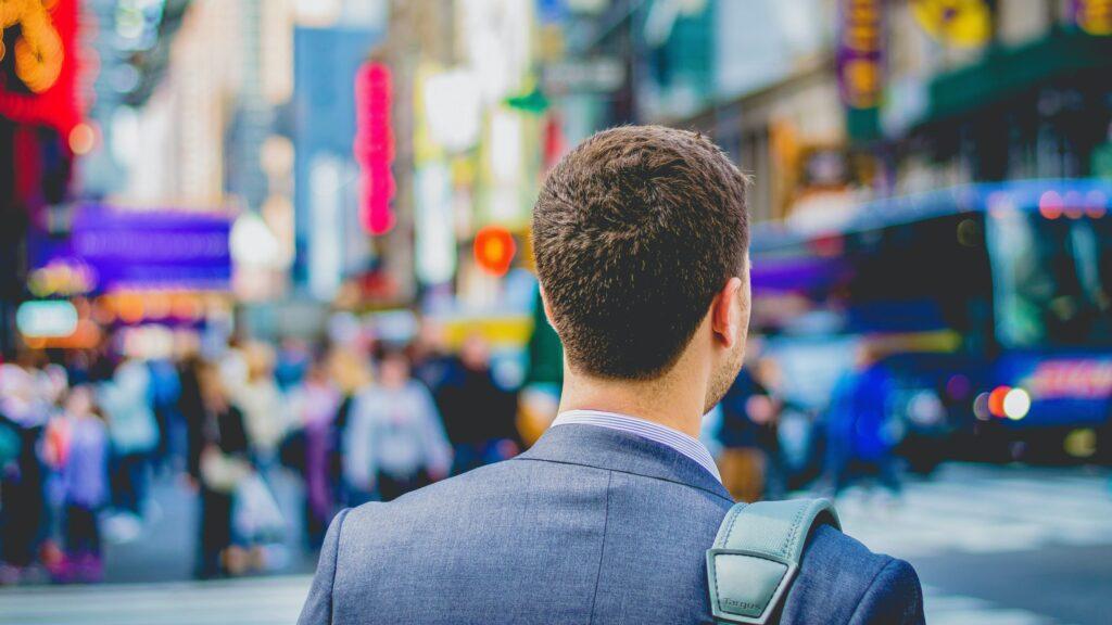 都会の中で立つスーツ姿の男性の後ろ姿