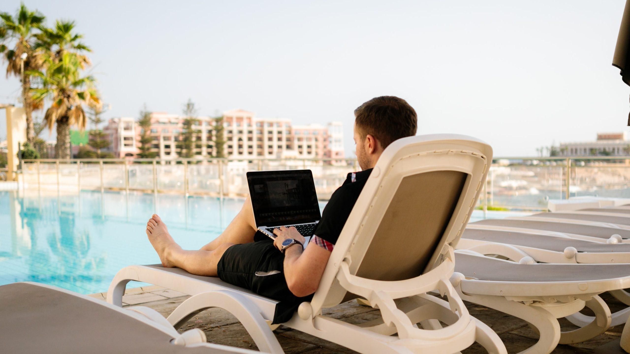 男性がプールサイドでパソコンを操作している画像