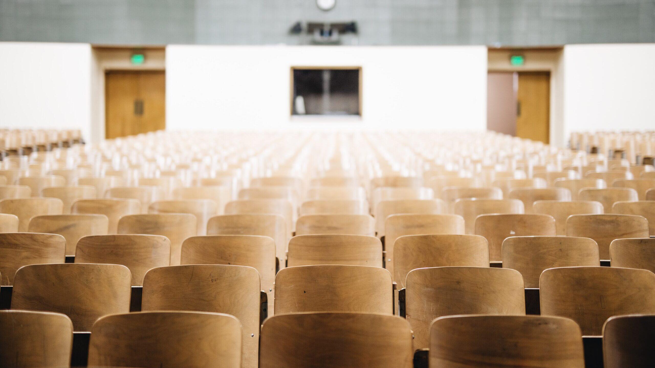 大学の講堂で多くの椅子が並んでいる写真